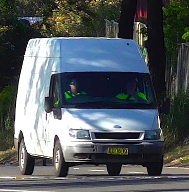 Courier van in a suburban street delivering parcels and other bulky freight items to their destination.